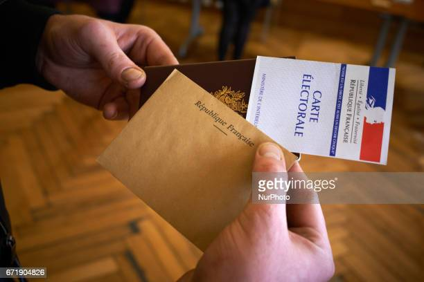 A man shows his passport his voter card and his ballot bedore casting his vote at the Capitole's polling station for the first round of the French...
