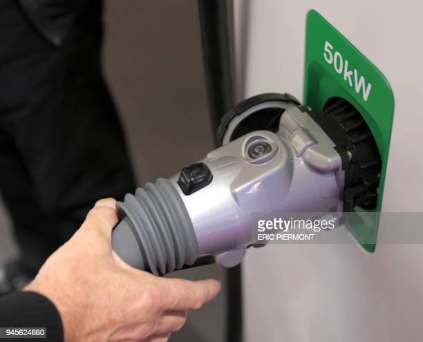 A man shows how tyo use a Schneider Electric recharging spot for electric cars at the Paris Auto Show on the first day of the twoday press days on...