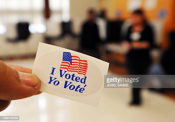 A man shows I voted sticker as others vote for midterm general elections at a polling station in Silver Spring Maryland on November 2 2010 President...