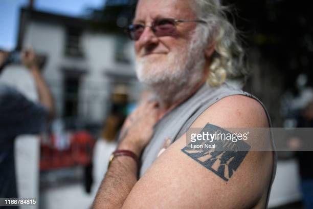 A man shows off his tattoo fifty years since the iconic album cover for Abbey Road by the Beatles was taken as he stands outside the studios on...