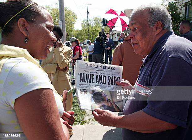 A man shows page one of The Plain Dealer newspaper to a friend while people gather along Seymour Avenue near the house where three women who...