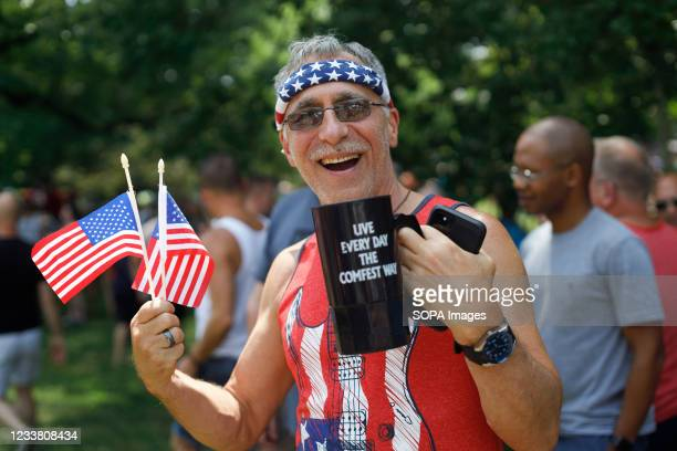 Man shows patriotism with all the American flags he is wearing. The Doo Dah Parade, a Fourth of July tradition in Columbus, Ohio, brings masses of...