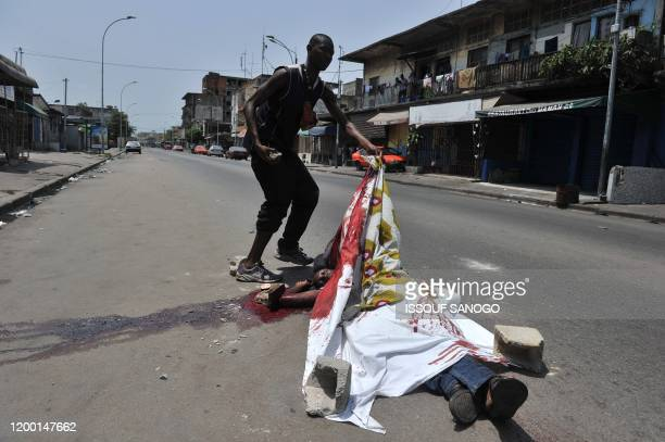 Man shows the body of a civilian who was killed on February 21, 2011 in a street of Treichville in Abidjan, in clashes between forces loyal to...