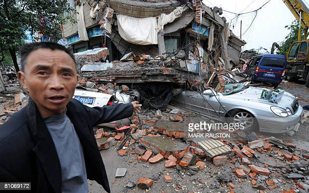 A man shows the damage to cars and buildings a day after a 78 magnitude earthquake hit the town of Hanwang in Sichuan Province on May 13 2008 China's...