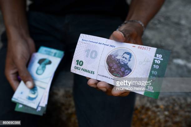 A man shows the new local community currency the panal launched in the '23 de Enero' workingclass neighbourhood in Caracas on December 15 2017 A...