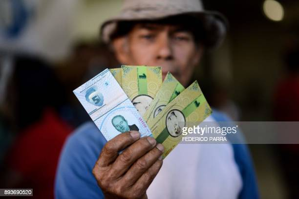 A man shows the new local community currency the panal launched in the 23 de Enero workingclass neighbourhood in Caracas on December 15 2017 A...