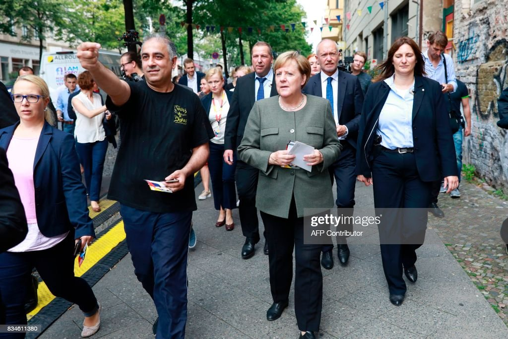 A man shows the way to German Chancellor and head of the Christian Democrats party Angela Merkel as she visits some shops in Berlin- Mitte district after the opening of the so-called 'walkable campaigning program' in Berlin, on August 18, 2017. / AFP PHOTO / Odd ANDERSEN