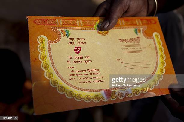 A man shows the wedding invitation of his daughter in a slum near a newly dug roadway April 22 2009 where agricultural areas he and members of twelve...