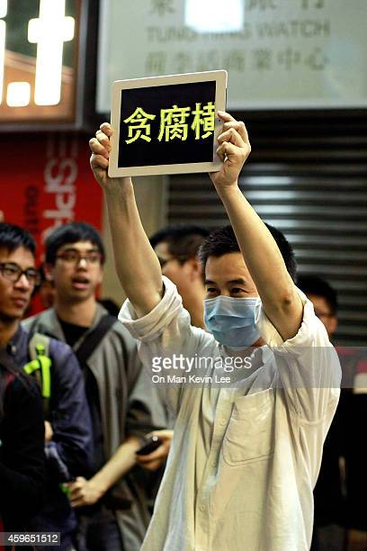 """Man shows the word """"corruption"""" in the Chinese characters used in mainland China on a street in Mongkok on November 27, 2014 in Hong Kong, Hong Kong...."""