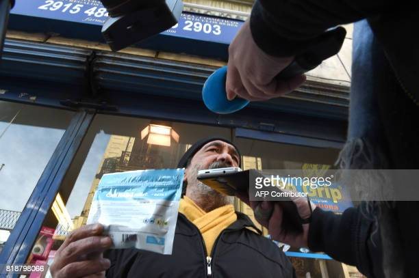 A man shows to the journalists an envelope containing marijuana he has just purchased at a pharmacy in Montevideo on July 19 2017 Pharmacies in...