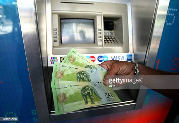 Man shows Venezuela's new 'bolivar fuerte' notes, at a cash dispenser in Caracas, on January 2nd a day after the new currency went into circulation....
