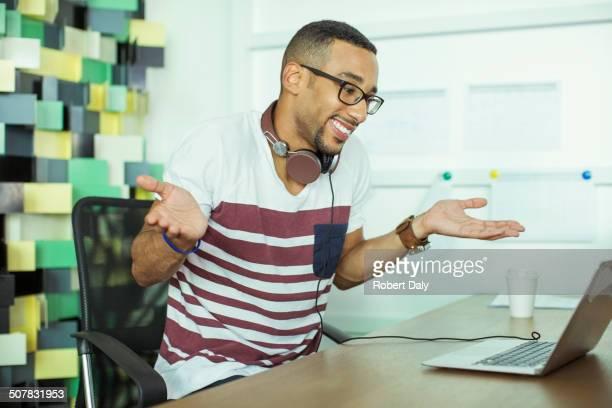 Man shrugging at laptop in office