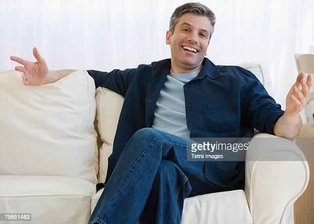 Man shrugging shoulders on sofa