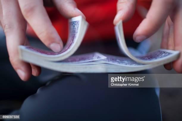 a man shuffles a deck of playing cards. - barajar fotografías e imágenes de stock