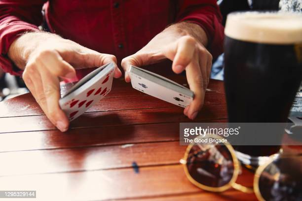 man shuffling a deck of cards in a pub in ireland - galway stock pictures, royalty-free photos & images
