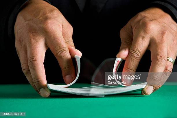 man shuffling deck of cards, close-up - shuffling stock photos and pictures
