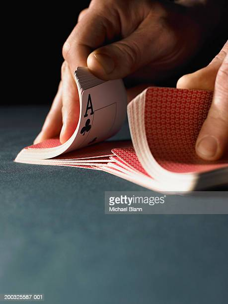 man shuffling playing cards, close-up - shuffling stock photos and pictures