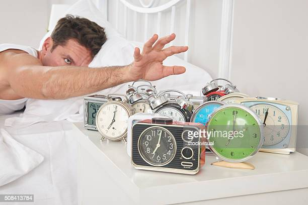 man shutting off alarm clocks - alarm stock photos and pictures