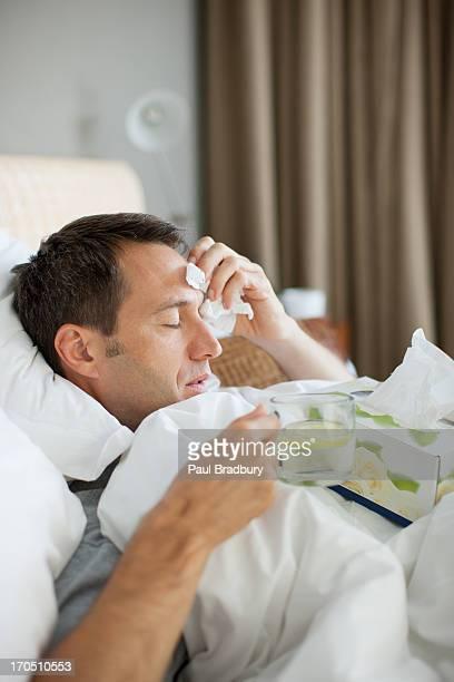 Krank im Bett Mann trinkt heißes Getränk
