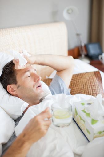 Man sick in bed drinking hot drink - gettyimageskorea