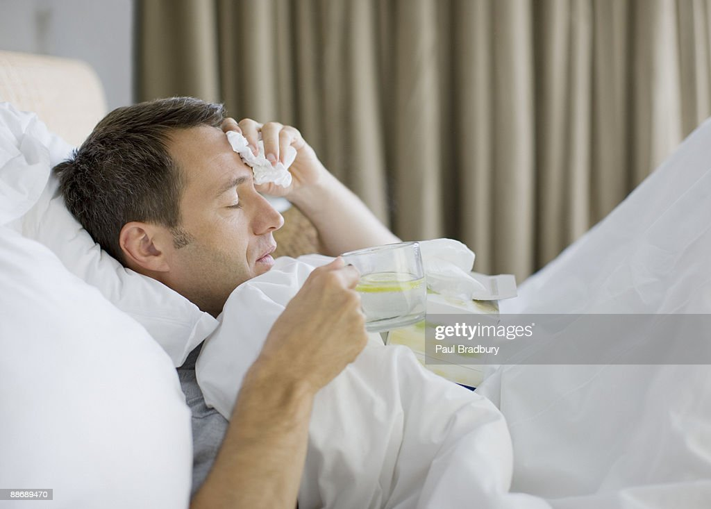 Man sick in bed drinking hot drink : Stock Photo