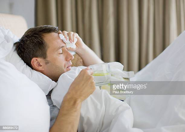 man sick in bed drinking hot drink - fever stock pictures, royalty-free photos & images