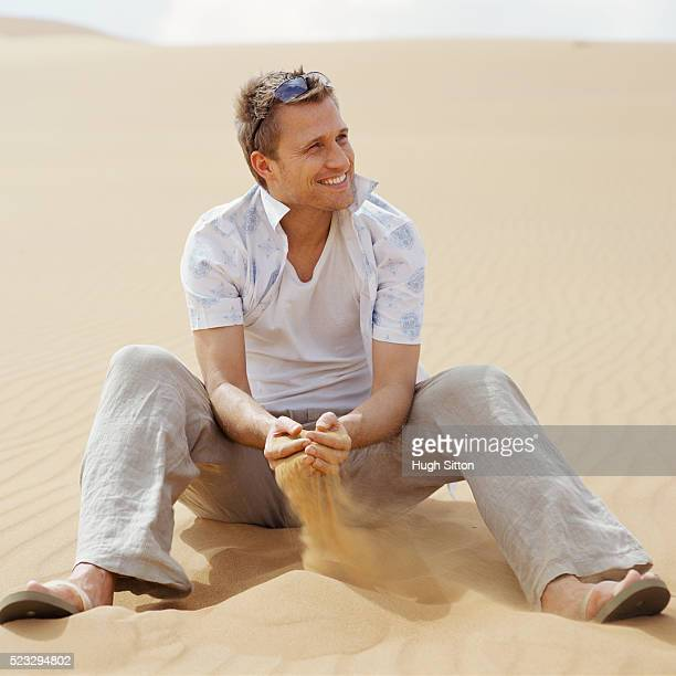 man sieving sand with his hands - hugh sitton stock pictures, royalty-free photos & images