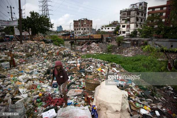 A man sifts through garbage next to a polluted canal that leads to the Buriganga river June 10 2018 in Dhaka Bangladesh Bangladesh has been...