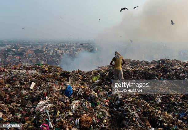 TOPSHOT A man sifts through trash at a massive garbage site in New Delhi on September 27 2016 Polluted air is a 'public health emergency' the World...