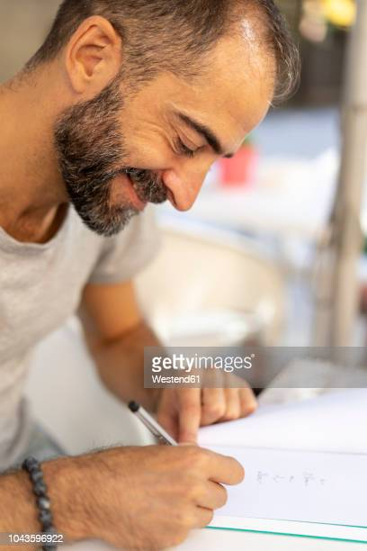 man signing a book - authors photos et images de collection