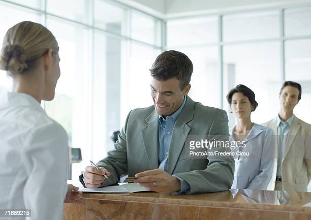 man signing at reception desk while people wait in line behind him - bureaucracy stock pictures, royalty-free photos & images