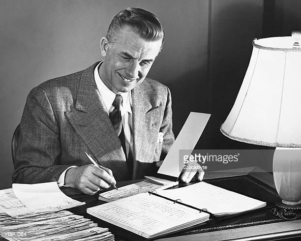 mann, die unterzeichnung schecks - formelle geschäftskleidung stock-fotos und bilder