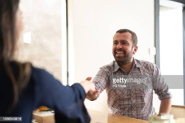 man signing contracts and handshake with a business woman - recruiter stock pictures, royalty-free photos & images