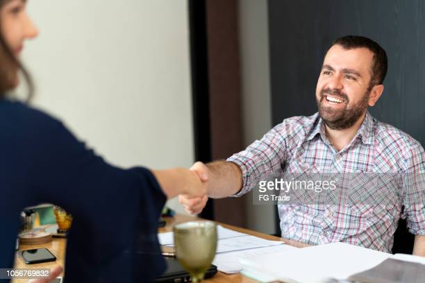 man signing contracts and handshake with a business woman - recruitment stock pictures, royalty-free photos & images