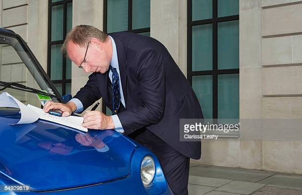 Man signing document on car bonnet