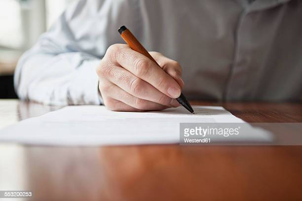man signing document - handwriting stock pictures, royalty-free photos & images
