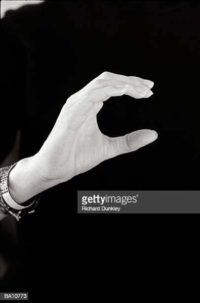 Man signing letter c in British sign language, close-up (B&W)