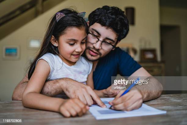 man signing papers with daughter in his lap - form filling stock pictures, royalty-free photos & images