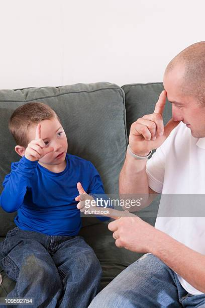 Man signing the word 'Brother' in American Sign Language while communicating with his son