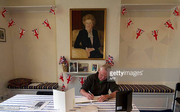 A man signs a book of condolence below a portrait of former British prime minister Margaret Thatcher at the Conservative Party headquarters in...
