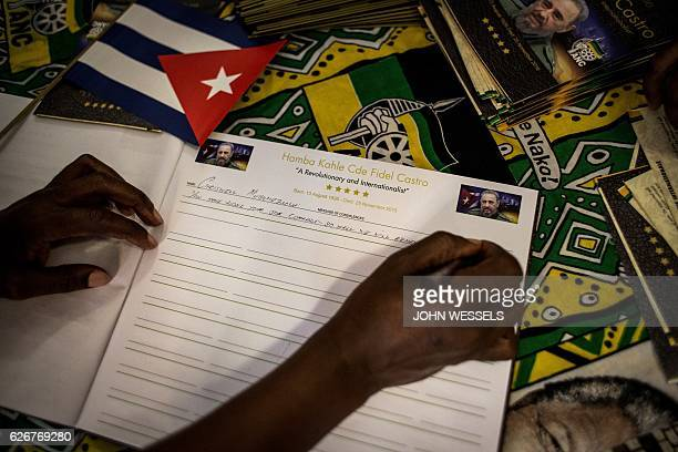 A man signs a book of condolence during a memorial for the late Cuban leader Fidel Castro held by South African ruling party African National...