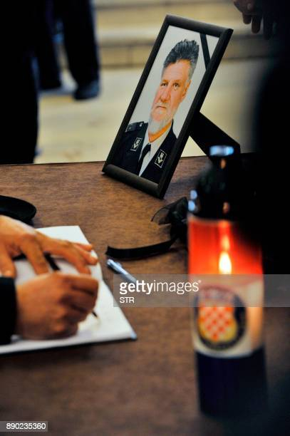 A man signs a condolence book before the start of a commemoration ceremony honouring the late Croatian general Slobodan Praljak in Zagreb on December...