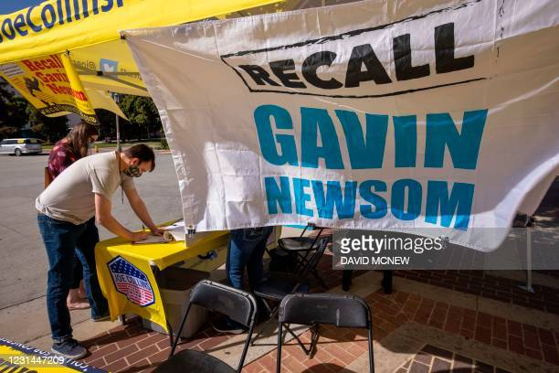 Man signs a petition as conservative activists gather signatures in a recall effort against California Governor Gavin Newsom near Pasadena City Hall,...