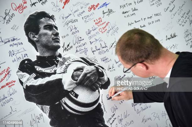 A man signs a poster of Brazilian's F1 driver Ayrton Senna during a ceremony on May 1 2019 marking the 25th anniversary of the death of Brazilian's...