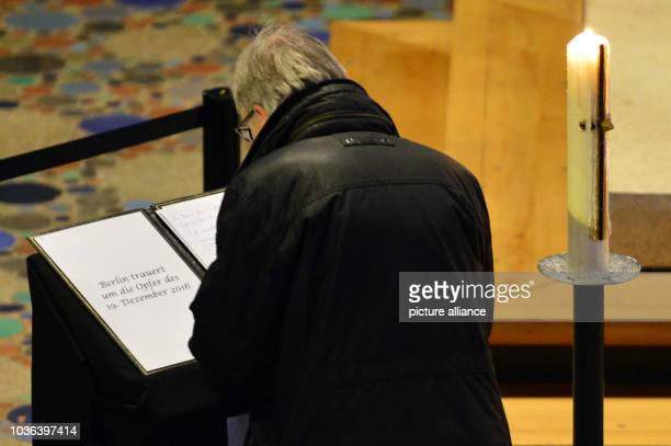 A man signs the book of condolence for the victims of the suspected attack on the Christmas market in the Kaiser Wilhelm Memorial Church in Berlin...