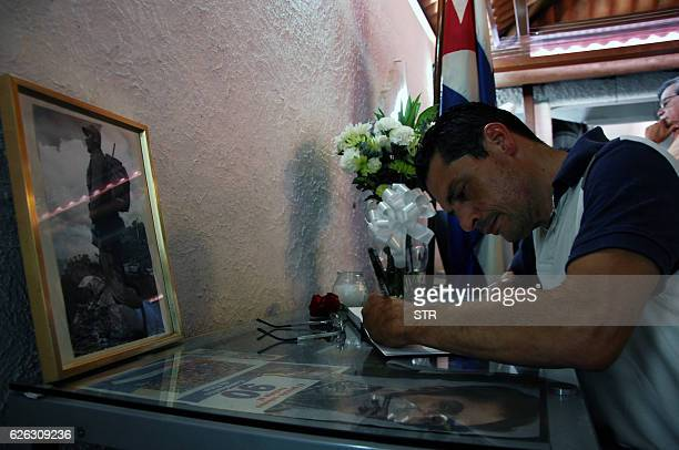 A man signs the condolence book at the Cuban embassy in Panama City on November 28 2016 Cuban revolutionary icon Fidel Castro died last Friday in...