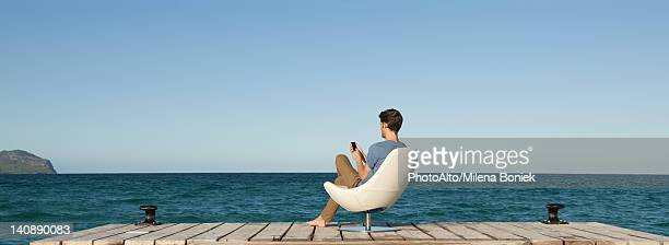 Man siitng in chair on dock using cell phone, rear view