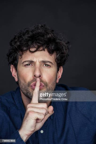 Man silencing with finger held to lips