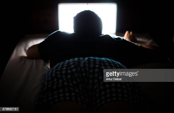 Man silhouette at dark night with laptop screen