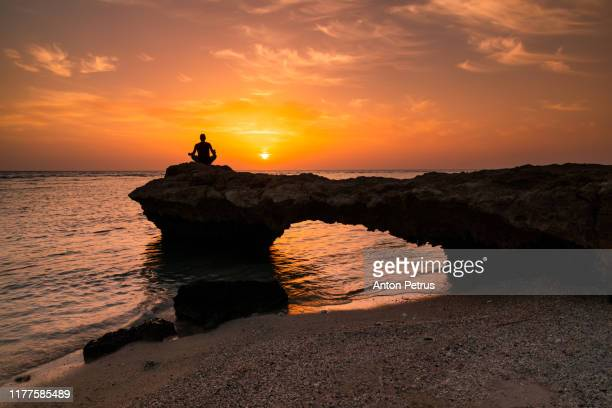 man silhouette doing yoga exercise at sunset beach - india summer stock-fotos und bilder